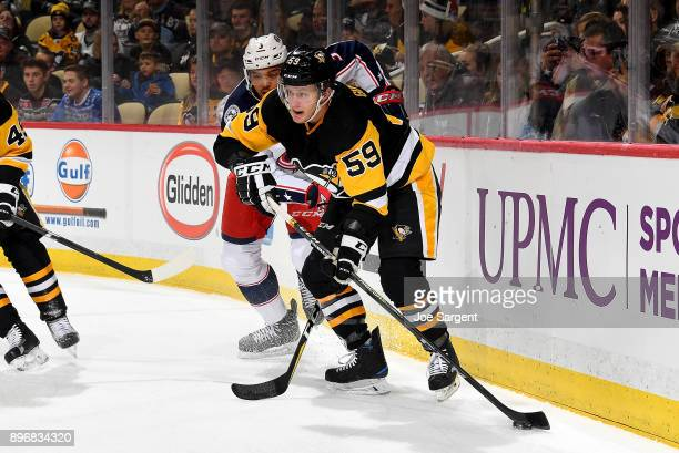 Jake Guentzel of the Pittsburgh Penguins handles the puck against Seth Jones of the Columbus Blue Jackets at PPG Paints Arena on December 21 2017 in...