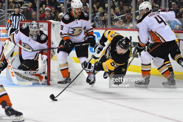 Jake Guentzel of the Pittsburgh Penguins reaches for the puck against the Anaheim Ducks at PPG PAINTS Arena on December 23 2017 in Pittsburgh...