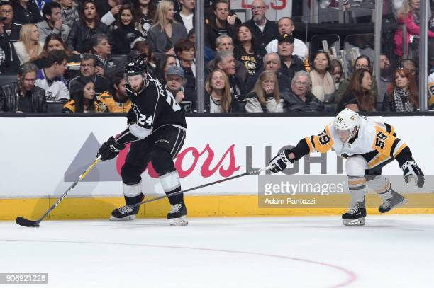Jake Guentzel of the Pittsburgh Penguins reaches for the puck against Derek Forbort of the Los Angeles Kings at STAPLES Center on January 18 2018 in...