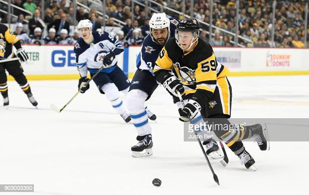 Jake Guentzel of the Pittsburgh Penguins skates with the puck against Dustin Byfuglien of the Winnipeg Jets during the game at PPG PAINTS Arena on...