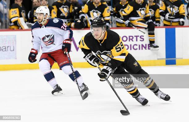Jake Guentzel of the Pittsburgh Penguins skates with the puck in the overtime period during the game against the Columbus Blue Jackets at PPG Paints...