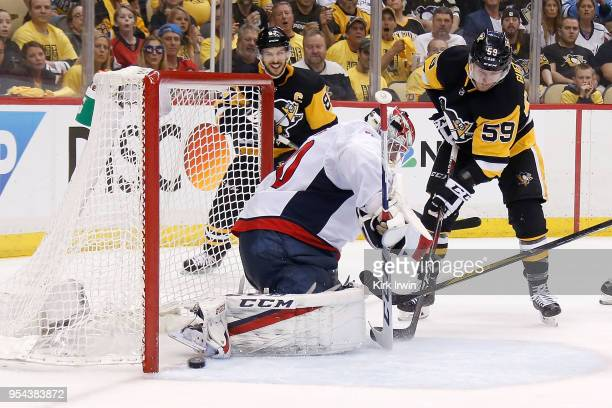 Jake Guentzel of the Pittsburgh Penguins slides the puck past Braden Holtby of the Washington Capitals for a goal during the second period in Game...