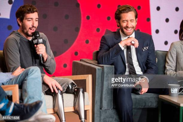 Jake Gyllenhaal laughs as Jeff Bauman speaks during the press conference for Stronger at the Toronto International Film Festival in Toronto on...