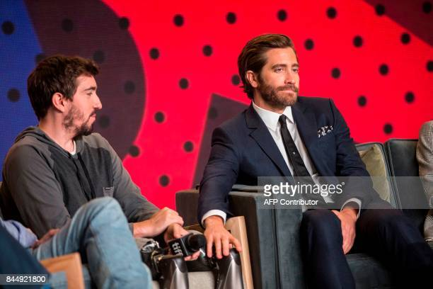 Jake Gyllenhaal strokes Jeff Bauman's artificial leg after being asked about a bromance between the two during the press conference for Stronger at...