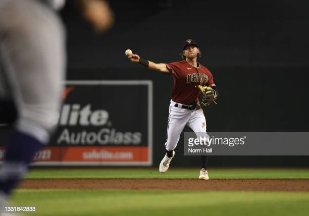 Jake Hager of the Arizona Diamondbacks makes a throw to first base for a force out on a ground ball hit by Julio Urias of the Los Angeles Dodgers...