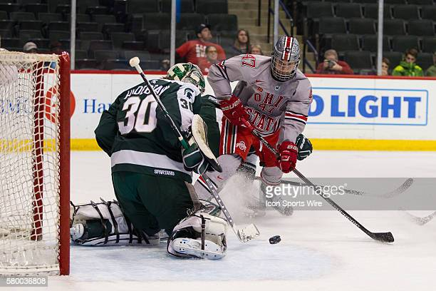 Jake Hildebrand of the Michigan State Spartans makes a save on Josh Healey of the Ohio State Buckeyes during the quarterfinal Big Ten men's ice...