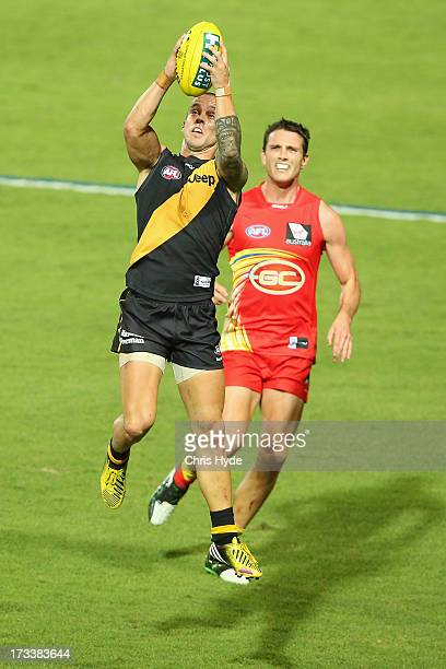 Jake King of the Tigers takes a mark over Tom Murphy of the Suns during the round 16 AFL match between the Richmond Tigers and the Gold Coast Suns at...