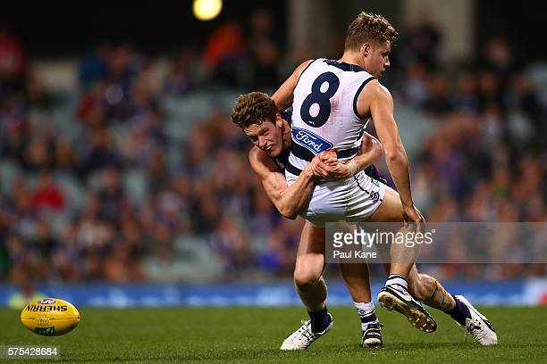 Jake Kolodjashnij of the Cats gets his handball away while being atckled by Matt Taberner of the Dockers during the round 17 AFL match between the...
