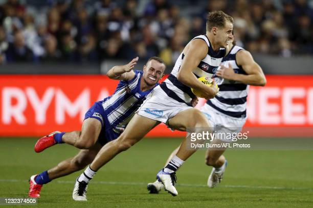 Jake Kolodjashnij of the Cats is tackled by Jack Mahony of the Kangaroos during the 2021 AFL Round 05 match between the Geelong Cats and the North...