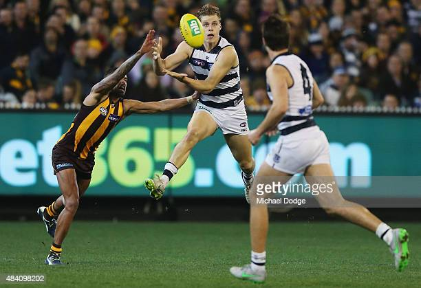 Jake Kolodjashnij of the Cats marks the ball against Bradley Hill of the Hawks during the round 20 AFL match between the Geelong Cats and the...