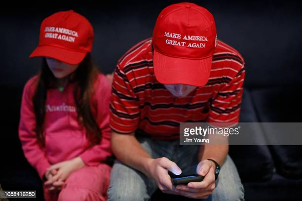 Jake Kriete right looks at his phone as he attends an election night rally for Republican Senate candidate Mike Braun on November 6 2018 in...