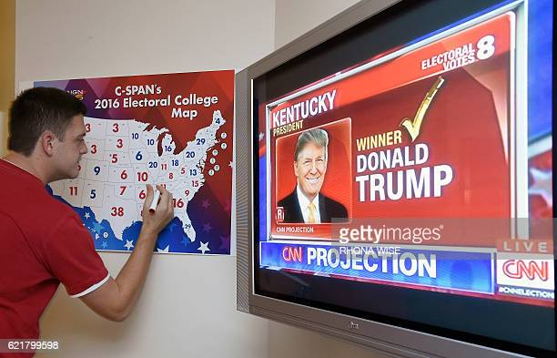 TOPSHOT Jake Krupa colors in an electoral map as states are projected for Republican presidential candidate Donald Trump or Democratic Presidential...