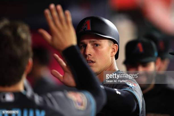 Jake Lamb is congraulated in the dugout after scoring on an RBI double by David Peralta of the Arizona Diamondbacks during the fifth inning of a game...