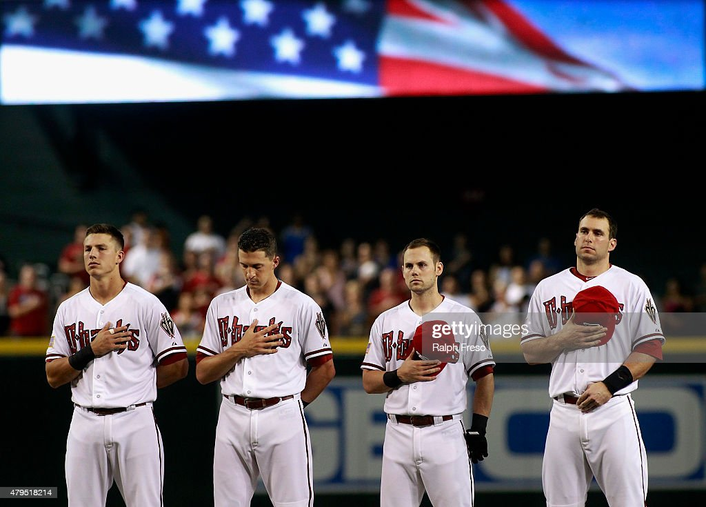 Jake Lamb #19, Nick Ahmed #13, Chris Owings #16 and Paul Goldschmidt #44 of the Arizona Diamondbacks stand during the National Anthem before the start of a MLB game against the Colorado Rockies at Chase Field on July 4, 2015 in Phoenix, Arizona.