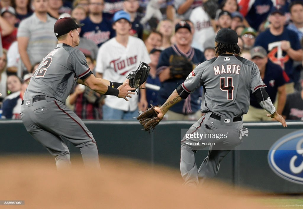 Jake Lamb #22 of the Arizona Diamondbacks makes a catch in foul territory of the ball hit by Eduardo Escobar #5 of the Minnesota Twins as teammate Ketel Marte #4 looks on during the seventh inning of the game on August 19, 2017 at Target Field in Minneapolis, Minnesota. The Twins defeated the Diamondbacks 5-0.