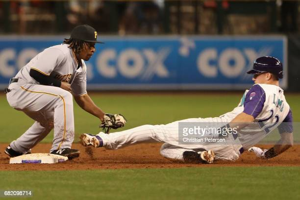 Jake Lamb of the Arizona Diamondbacks safely slides into second base ahead of the tag from infielder Gift Ngoepe of the Pittsburgh Pirates during the...