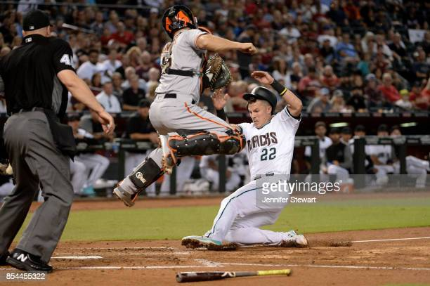 Jake Lamb of the Arizona Diamondbacks safely slides to score against Nick Hundley of the San Francisco Giants in the second inning at Chase Field on...