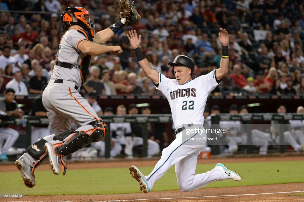 Jake Lamb #22 of the Arizona Diamondbacks safely slides to score against Nick Hundley #5 of the San Francisco Giants in the second inning at Chase Field on September 26, 2017 in Phoenix, Arizona.