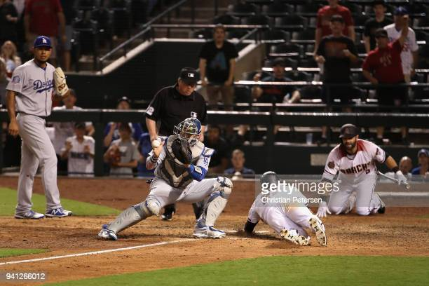 Jake Lamb of the Arizona Diamondbacks slides in safely to score a run past catcher Yasmani Grandal of the Los Angeles Dodgers during the 15th inning...