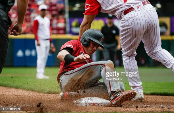 Jake Lamb of the Arizona Diamondbacks slides into third base as Eugenio Suarez of the Cincinnati Reds attempts to tag at Great American Ball Park on...