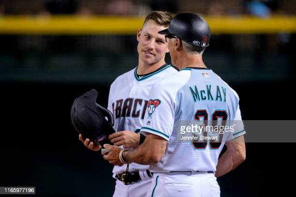 Jake Lamb of the Arizona Diamondbacks talks with first base coach Dave McKay in the third inning of the MLB game against the Milwaukee Brewers at...