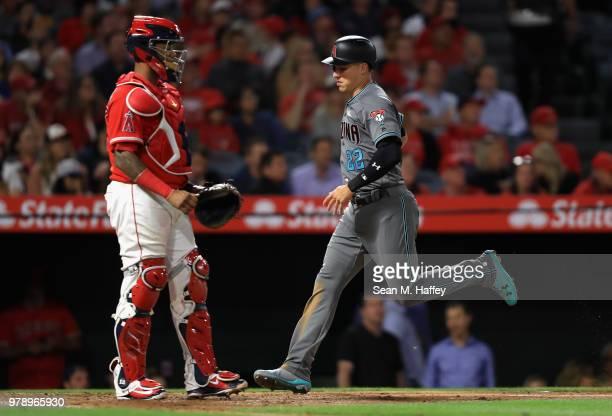 Jake Lamb scores on an RBI double hit by David Peralta of the Arizona Diamondbacks as Martin Maldonado of the Los Angeles Angels of Anaheim looks on...