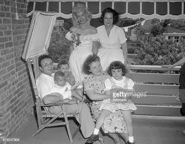 Jake Lamotta is seated with his family around him His wife Vicki is wearing a white dress off her shoulders