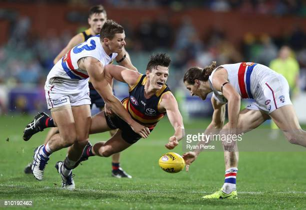 Jake Lever of the Crows competes for the ball against Jack Redpath and Marcus Bontempelli of the Bulldogs during the round 16 AFL match between the...