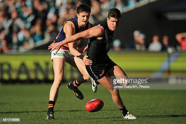 Jake Lever of the Crows tackles Paul Stewart of the Power during the 2015 AFL round 16 match between Port Adelaide Power and the Adelaide Crows at...