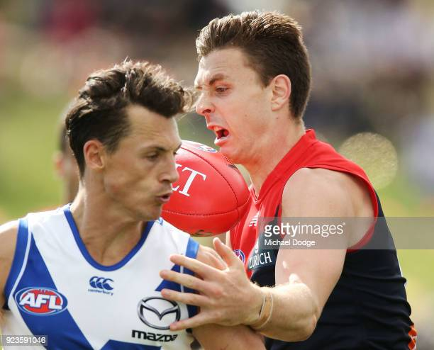 Jake Lever of the Demons gathers the ball from Ben Jacobs of the Kangaroos during the JLT Community Series AFL match between the North Melbourne...