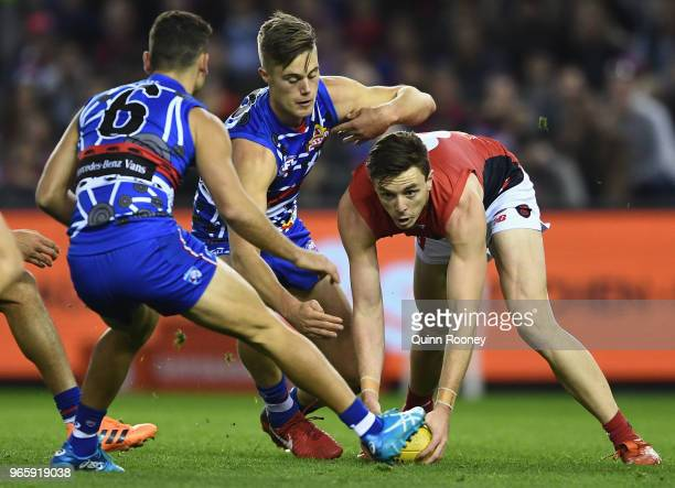Jake Lever of the Demons is tackled by Josh Schache of the Bulldogs during the round 11 AFL match between the Western Bulldogs and the Melbourne...
