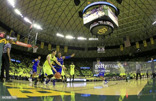 Jake Lindsey of the Baylor Bears dribbles the ball as Devonte' Graham of the Kansas Jayhawks defends in the first half at the Ferrell Center on...
