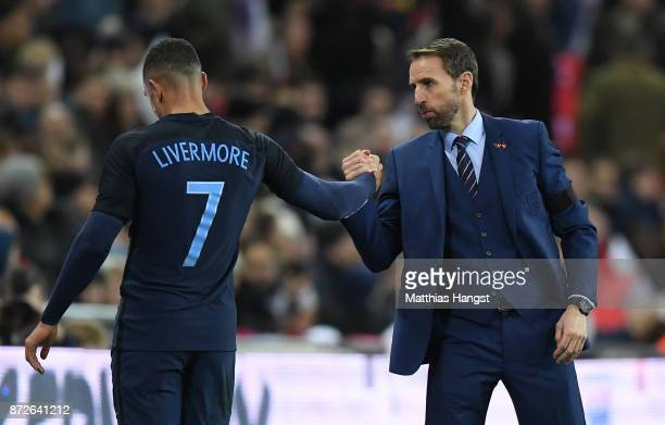 Jake Livermore of England shakes hands with Gareth Southgate Manager of England after he is subbed during the International friendly match between...