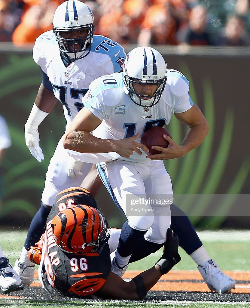 Jake Locker #10 of the Tennessee Titans is sacked by the Carlos Dunlap #96 of the Cincinnati Bengals during the game at Paul Brown Stadium on September 21, 2014 in Cincinnati, Ohio.