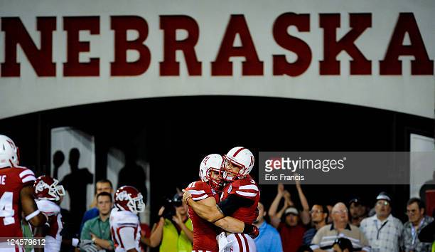 Jake Long congratulates Taylor Martinez of the Nebraska Cornhuskers after scoring a late touchdown to seal the win over Fresno State during their...
