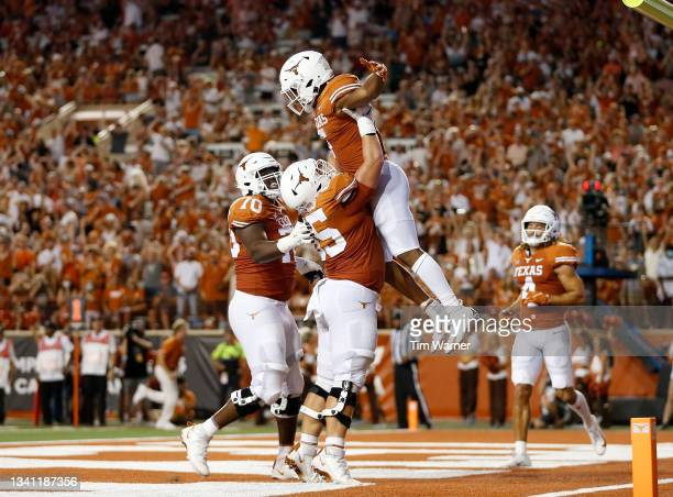 Jake Majors of the Texas Longhorns lifts Bijan Robinson in celebration after a touchdown in the second quarter against the Rice Owls at Darrell K...