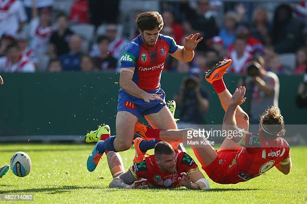 Jake Mamo of the Knights and Josh Dugan of the Dragons watch on as Mitch Rein of the Dragons falls after scoring a try during the round 21 NRL match...