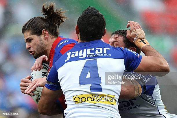 Jake Mamo of the Knights is tackled by the Bulldogs defence during the round 22 NRL match between the Newcastle Knights and the Canterbury Bulldogs...
