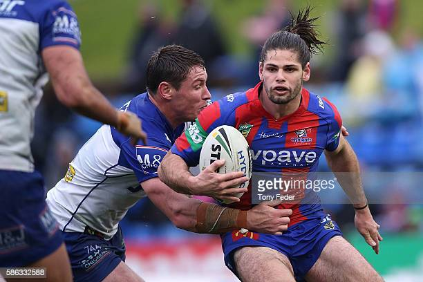Jake Mamo of the Knights is tackled during the round 22 NRL match between the Newcastle Knights and the Canterbury Bulldogs at Hunter Stadium on...