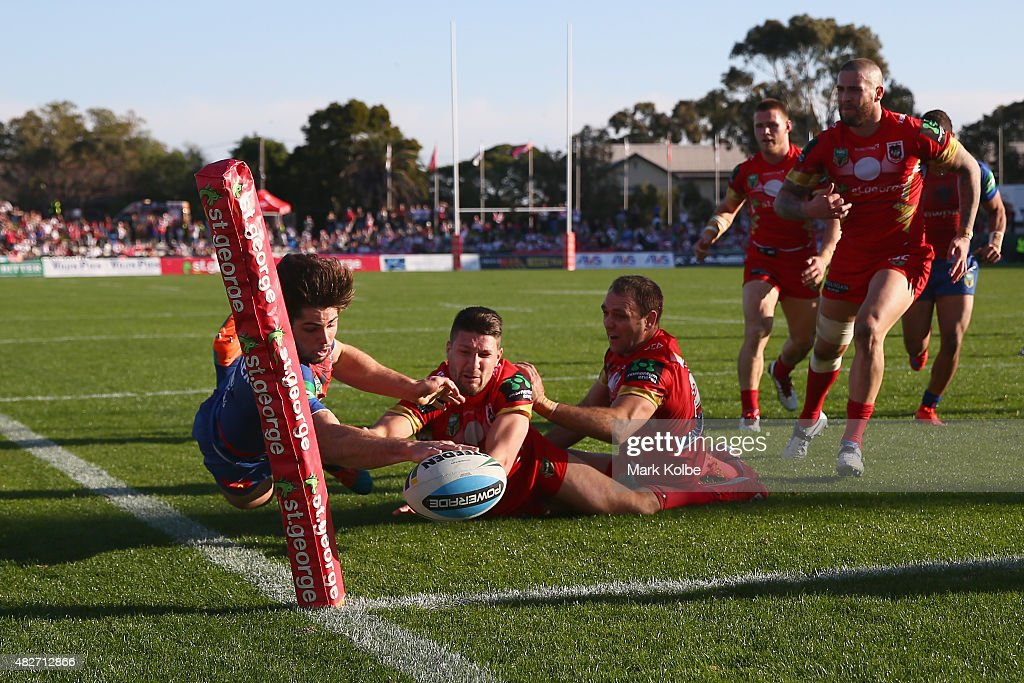 Jake Mamo of the Knights loses the ball as he stretches to score a try being tackled by Benji Marshall and Jason Nightingale of the Dragons during the round 21 NRL match between the St George Illawarra Dragons and the Newcastle Knights at WIN Jubilee Stadium on August 2, 2015 in Sydney, Australia.