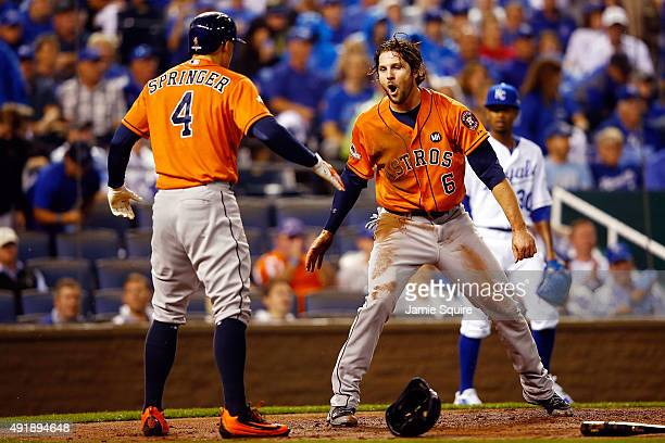 Jake Marisnick of the Houston Astros celebrates with George Springer of the Houston Astros after scoring a run on an RBI single hit by Jose Altuve of...