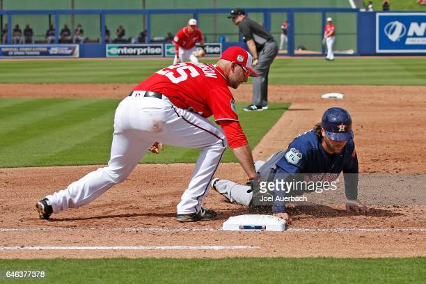 Jake Marisnick of the Houston Astros dives back to first base safe ahead of the tag by Clint Robinson of the Washington Nationals in the third inning...