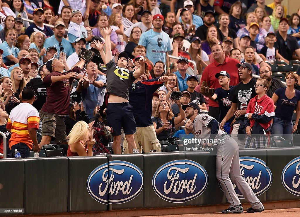 Jake Marisnick #6 of the Houston Astros hits the wall as fans reach for a foul ball during the fourth inning of the game on August 29, 2015 at Target Field in Minneapolis, Minnesota. The Astros defeated the Twins 4-1.