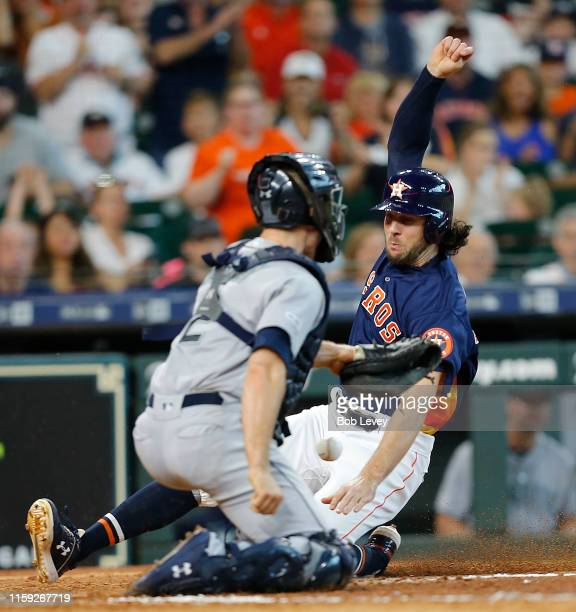 Jake Marisnick of the Houston Astros scores in the eighth inning as he slides around the tag attempt by Tom Murphy of the Seattle Mariners in the...