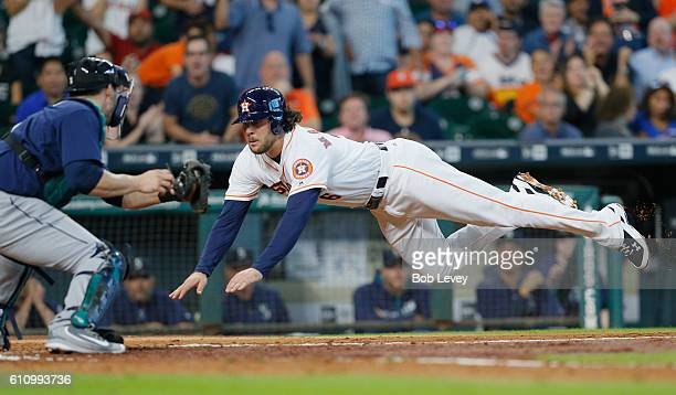 Jake Marisnick of the Houston Astros scores in the fifth inning as he avoids the tag by catcher Mike Zunino of the Seattle Mariners at Minute Maid...