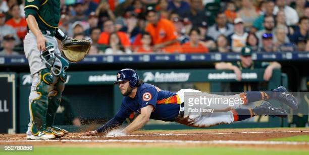 Jake Marisnick of the Houston Astros scores in the third inning on a sacrifice bunt by Jose Altuve against the Oakland Athletics at Minute Maid Park...