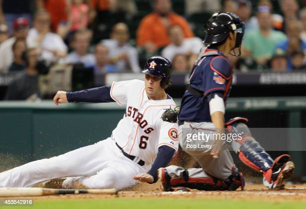 Jake Marisnick of the Houston Astros slides past Kurt Suzuki of the Minnesota Twins to score in the sixth inning at Minute Maid Park on August 12...