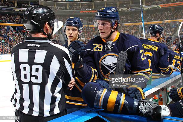 Jake McCabe and Brendan Guhle of the Buffalo Sabres talk to linesman Steve Miller during a video review in an NHL game at the KeyBank Center on...