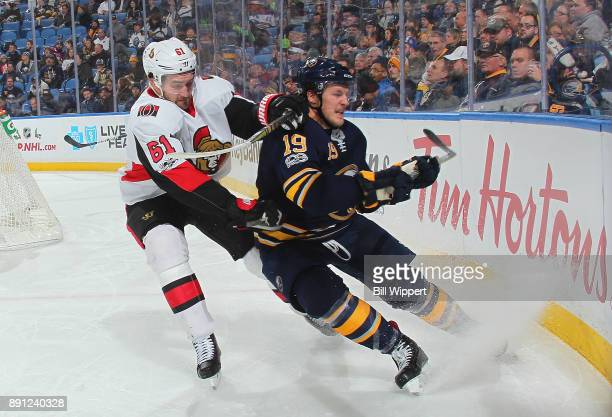 Jake McCabe of the Buffalo Sabres battles for the puck along the end boards against Mark Stone of the Ottawa Senators during an NHL game on December...