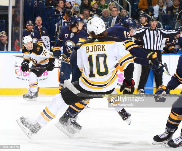 Jake McCabe of the Buffalo Sabres checks Anders Bjork of the Boston Bruins during an NHL game on December 19 2017 at KeyBank Center in Buffalo New...